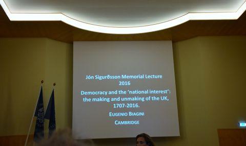 """Ekran z wyświetlonym tytułem wykładu prof. Eugenio F. Biaginiego: """"Democracy and the 'national interest': the making and the unmaking of the UK, 1707-2016"""""""
