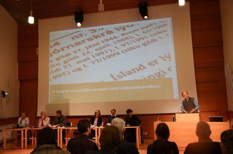Mężczyzna stojący przy mównicy występujący podczas debaty