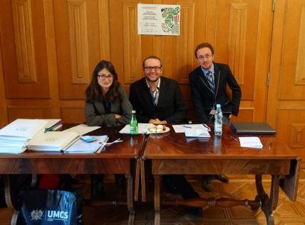 Trzech członków koła siedzących przy stole z materiałami konferencyjnymi