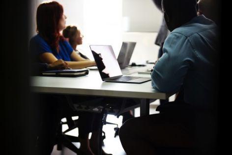 Element ilustracyjny: Grupa osób słuchająca wystąpienia, siedząca przy stole z laptopami. Photo by rawpixel.com on Unsplash