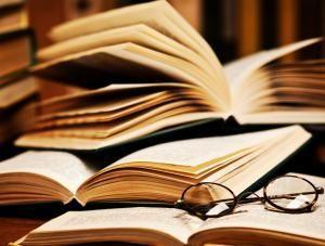 Okulary i otwarte książki leżące jedna na drugiej, całość w kolorze brązowo-kremowym.